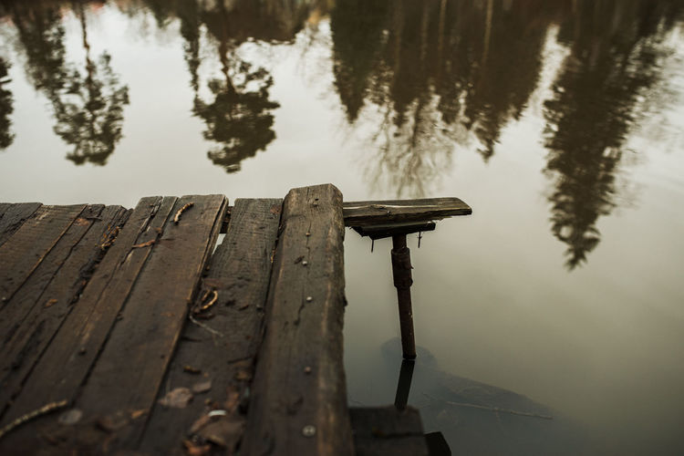 Wooden jetty on lake against sky