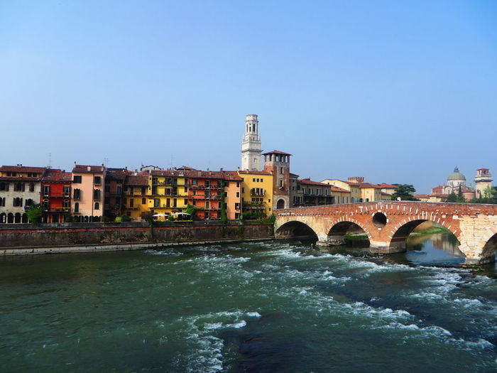 Ponte pietra over adige river against clear sky