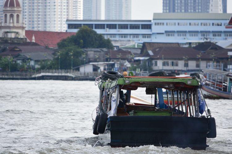 Boat in river by buildings in city
