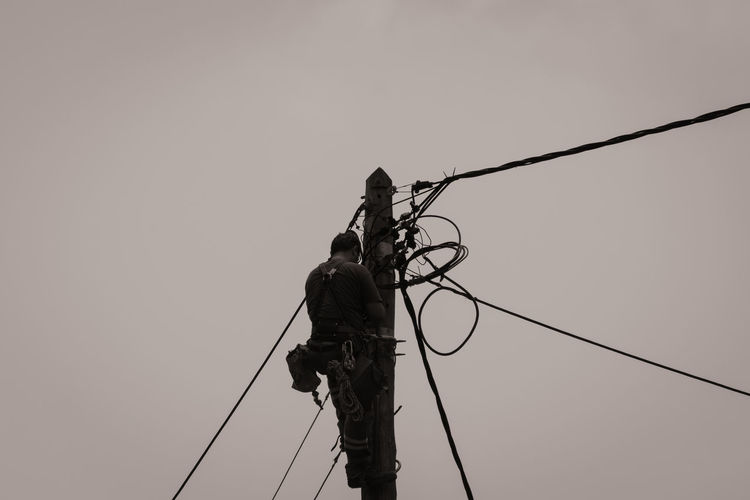 people at work.. Cable Clear Sky Connection Day Electricity  Full Length Low Angle View Men Nature One Person Outdoors People People At Work Real People RISK Rope Silhouette Sky Technology Business Stories