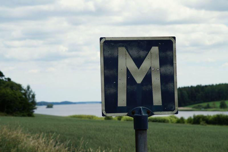 Letter M Sign On Grassy Field Against Sky