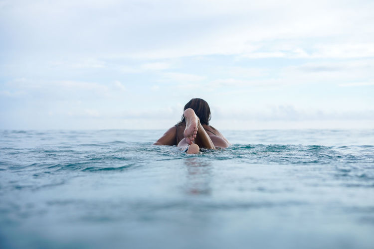 Woman swimming in sea against sky