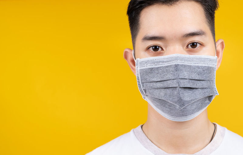 Portrait of young man against yellow background