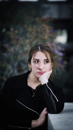 Close-up of young woman looking away while sitting outdoors