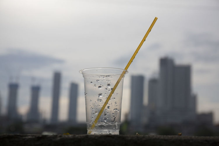 Plastic Cup and Straw Waste Plastic Environment - LIMEX IMAGINE PLASTIC CONTAINER Straw Drinking Straw Household Equipment No People Drinking Glass Skyscraper Pollution Water Still Life Close-up Focus On Foreground Glass Nature Day Sky Environment Isuues