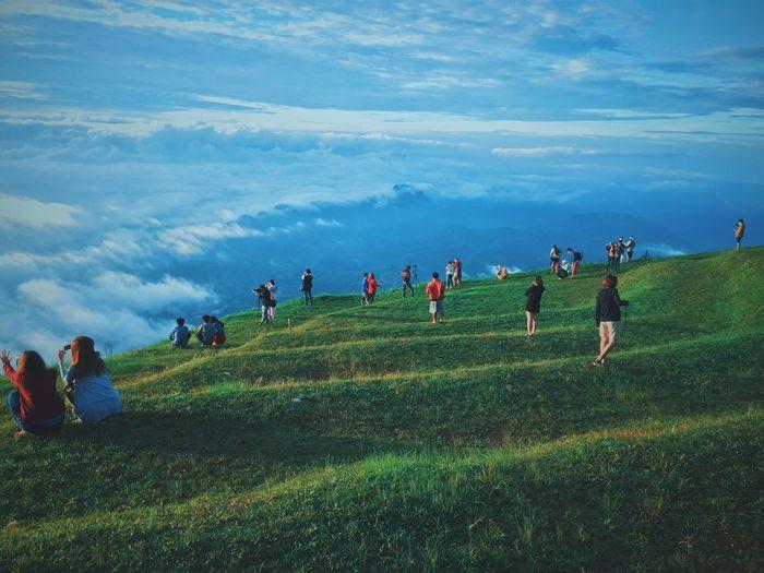 People enjoying at grassy landscape against sky