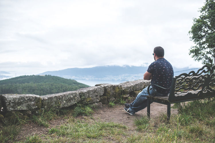 Rear view of man sitting on mountain looking at view
