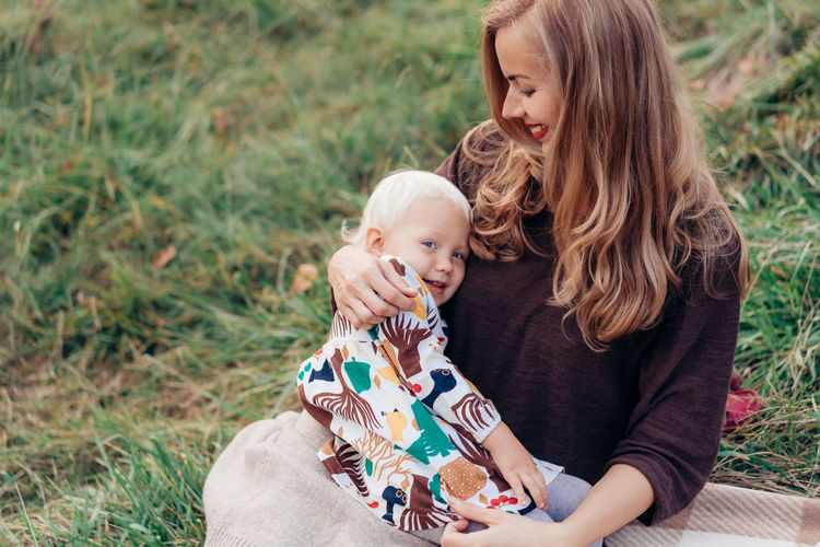 Mother with cute daughter sitting on grassy land