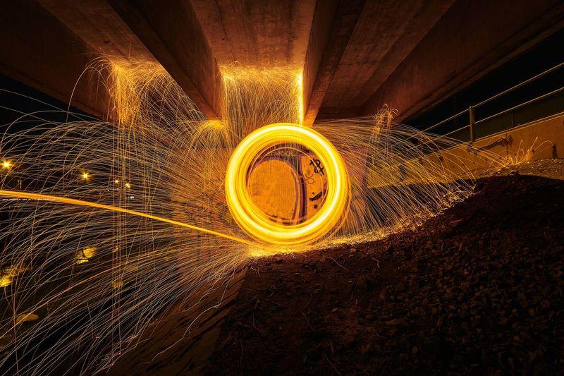 Wire wool spinning underneath bridge at night
