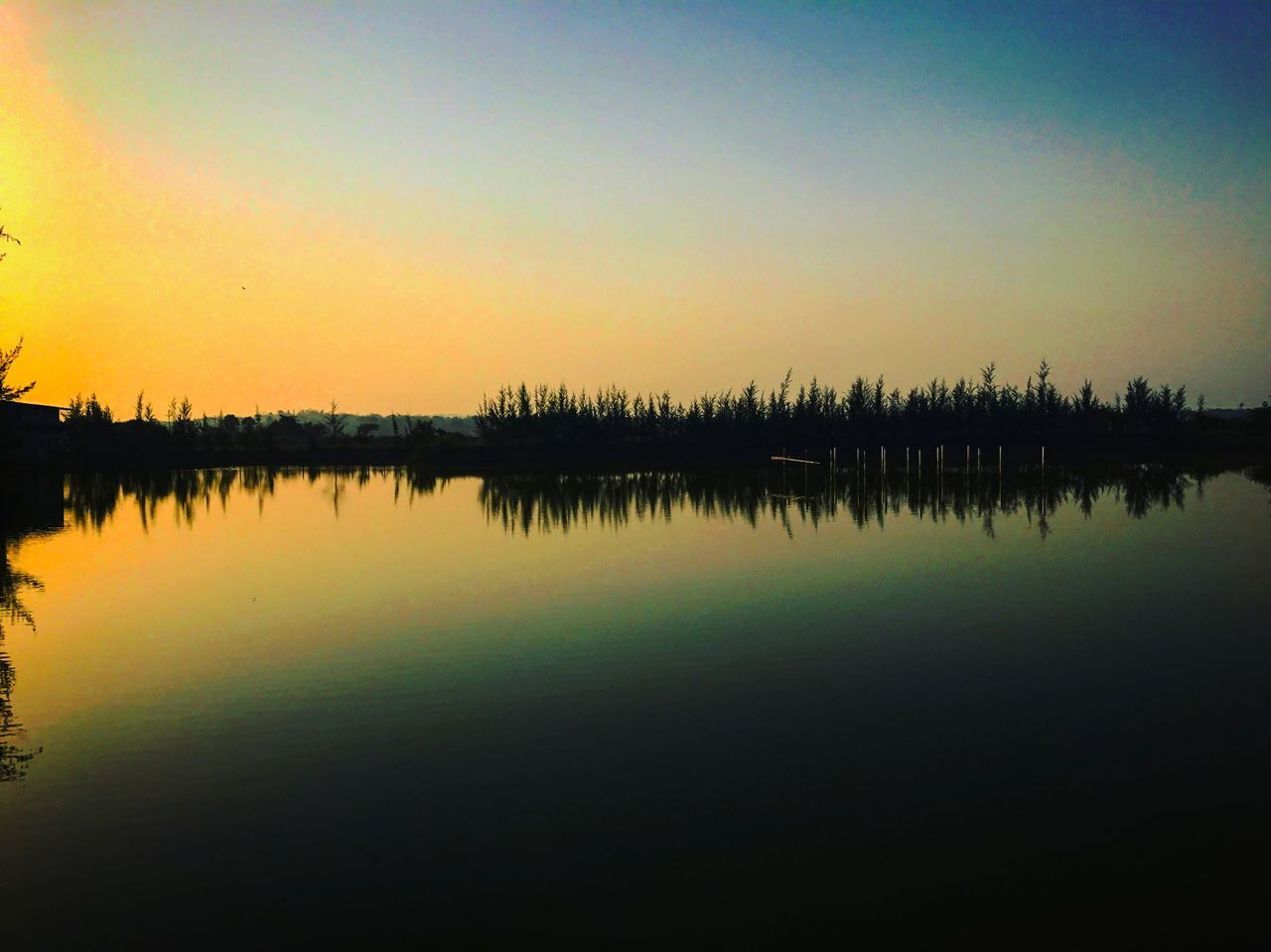 reflection, water, lake, tranquil scene, standing water, tranquility, nature, beauty in nature, scenics, silhouette, sunset, waterfront, outdoors, no people, sky, symmetry, day