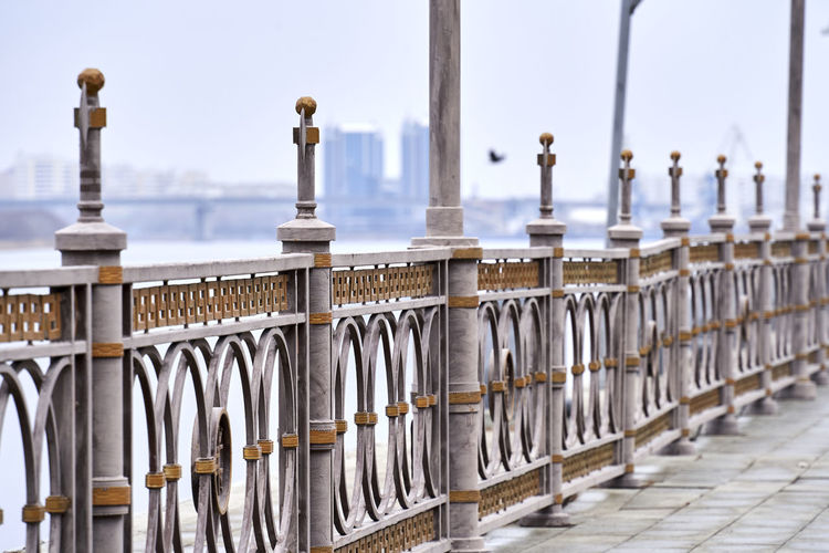 Row of metal railing against sky