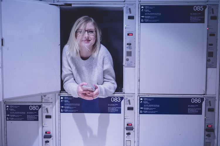 Portrait of young woman using in locker