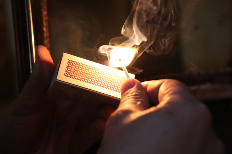 Close-Up Of Hand Igniting Matchstick In Darkroom