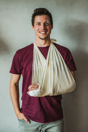 Portrait of smiling young man with fracture hand standing against wall