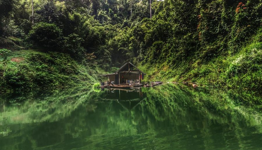 Deserted house floating in a dam jungle