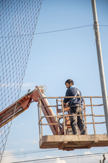 Low angle view of man working at construction site against sky