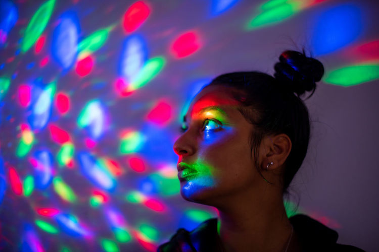Portrait of young woman wearing multi colored light painting