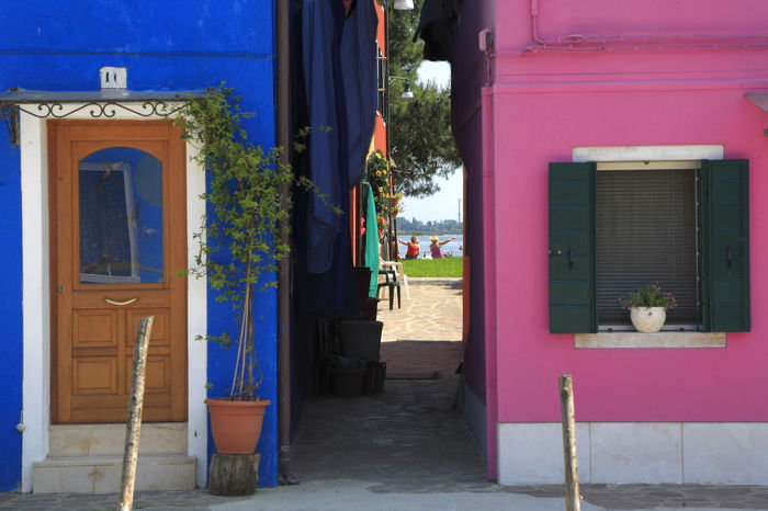Adapted To The City 2 Women Sitting On The Shore Finger Pointing View Through Buildings Colorful Houses Colorful Home Pink And Blue at Burano Island Venice Architecture Window Door Blue Entrance Outdoors Destinations ıtaly Travel Travel Destinations Blue House Street Photography Urban Exploration Fine Art In And Out Miles Away Minimalist Architecture The Street Photographer - 2017 EyeEm Awards