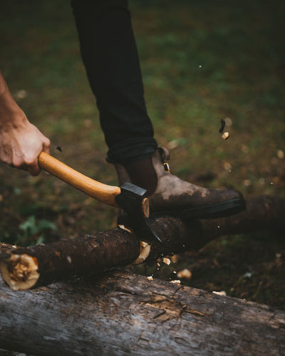 Low section of man cutting wood in forest