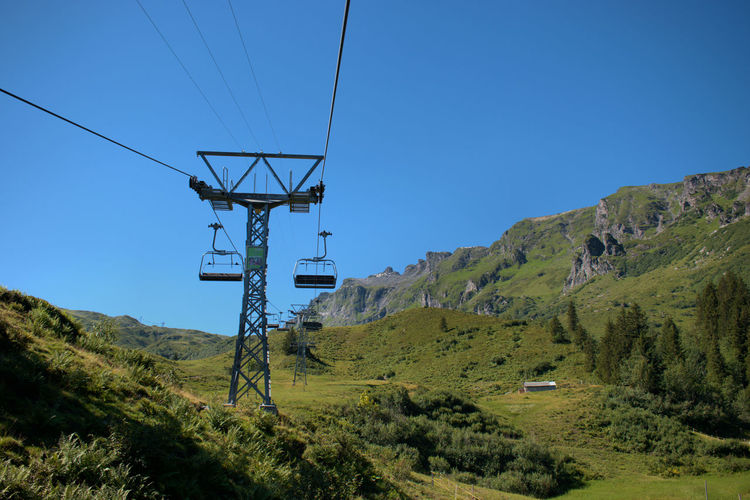 Overhead cable car on mountain against clear blue sky
