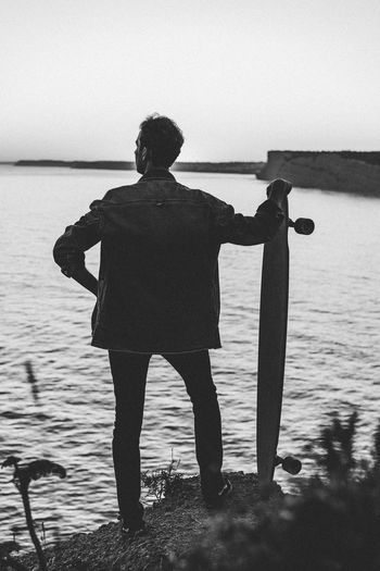 Standing One Person Lifestyles Looking At View Casual Clothing Men Longboard Cliff End Sea Romantic Black And White Adult Man Stylish Portugal Dreamer Travel NOMAD Watching Looking