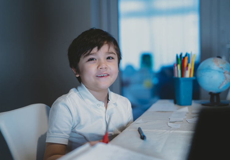 Portrait of smiling boy sitting on table