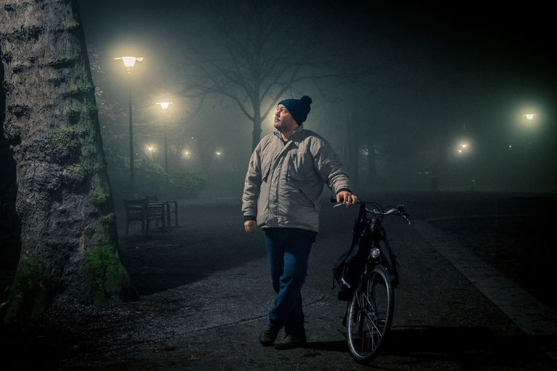 Man standing with bicycle at night