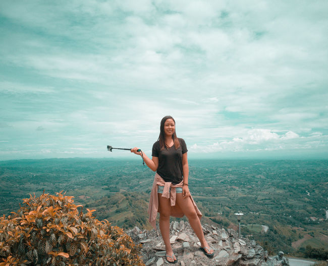 Portrait of smiling young woman standing on mountain against cloudy sky