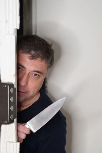 Portrait of thief with knife by door