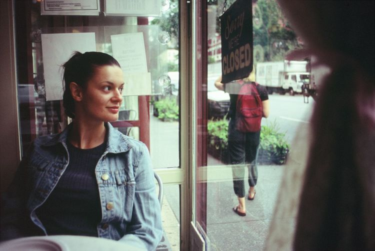 Real People Window Lifestyles Transparent Leisure Activity One Person Glass - Material Reflection Young Adult Casual Clothing Looking Day Women Portrait Adult Incidental People Waist Up Young Women Outdoors Contemplation Hairstyle Beautiful Woman Model New York Magnolia Bakery