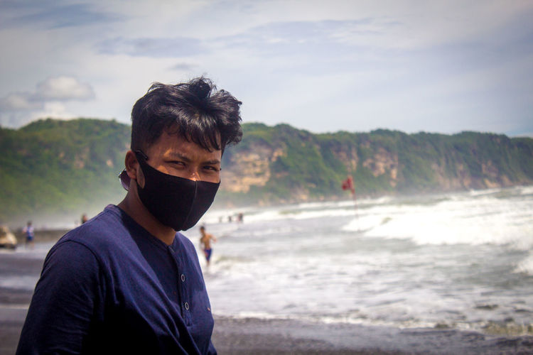 Portrait of a man standing on the beach, wearing a mask