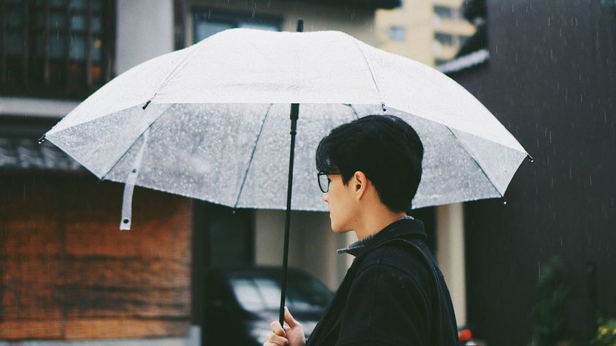 Man holding umbrella during rainy season