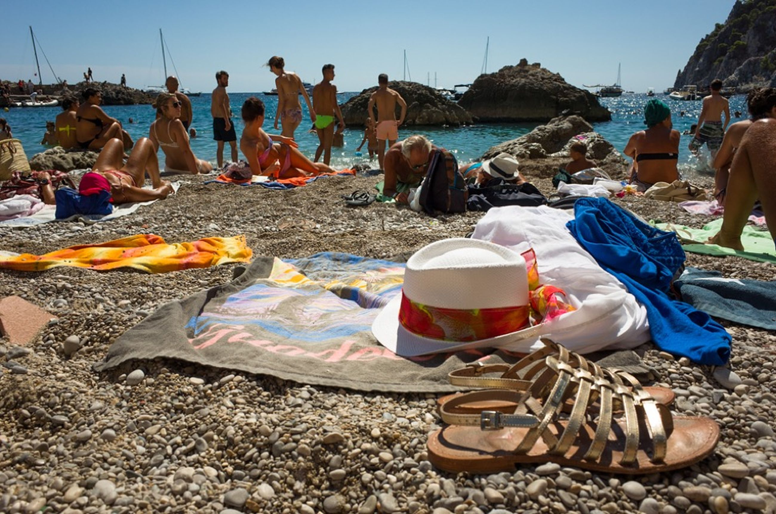 beach, sea, water, shore, sand, nautical vessel, moored, vacations, large group of people, sunlight, boat, beach umbrella, incidental people, transportation, tranquility, day, relaxation, nature, clear sky