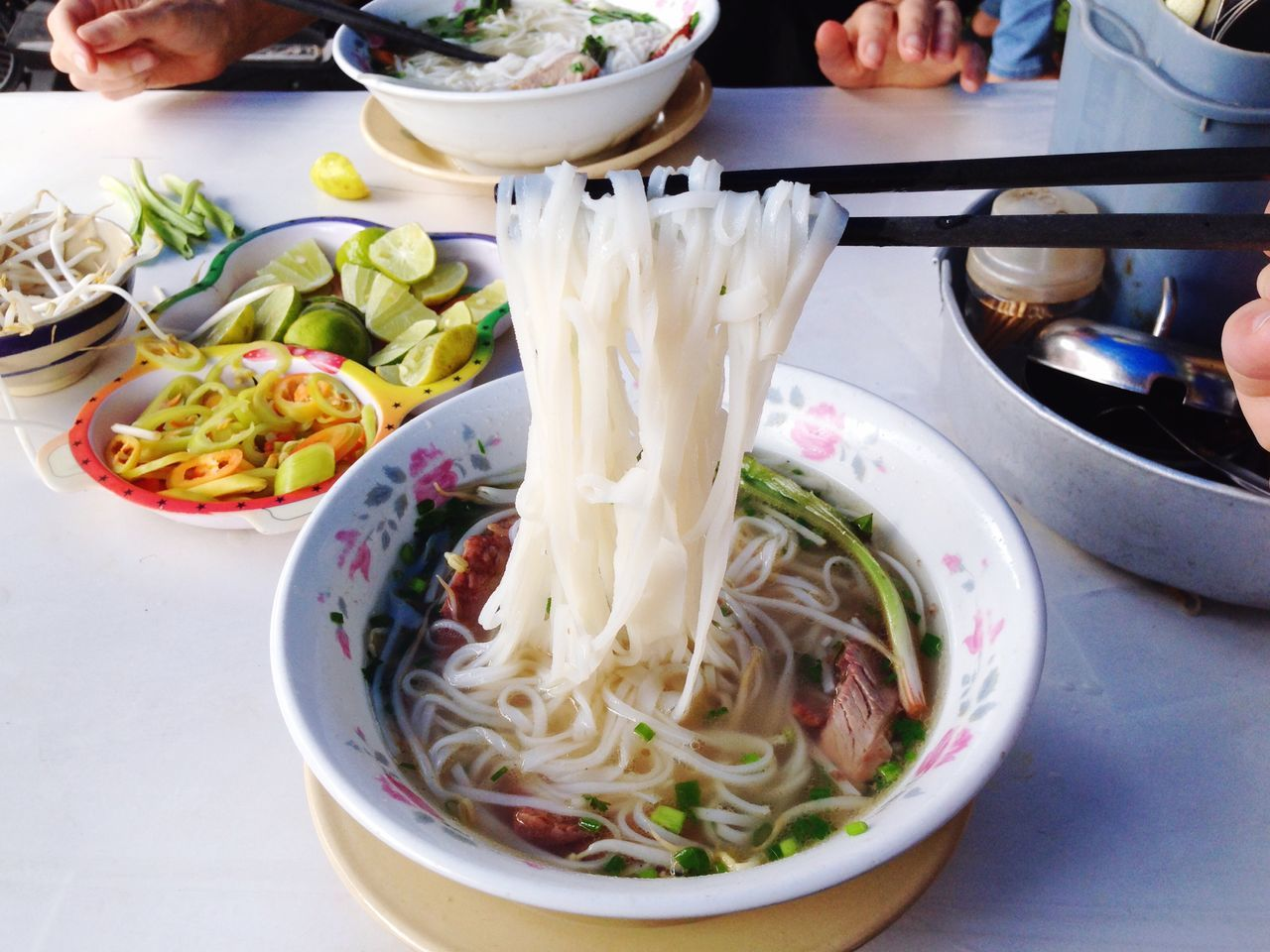 Chopsticks holding noodles in bowl on table
