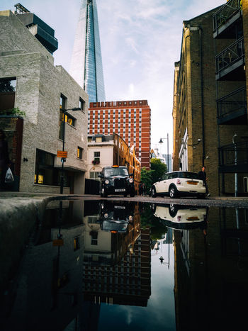 One of the shots I captured whilst exploring South East London with the Honor 10 City City Life EyeEm Best Shots London Taxi Transportation Architecture Building Building Exterior Built Structure City Cloud - Sky Day Honor 10 Outdoors Puddle Reflection Residential District Sky Skyscraper Streetphotography Tower Travel Destinations Urban Water