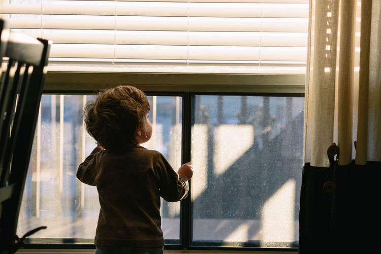 Boy Looking Through Window