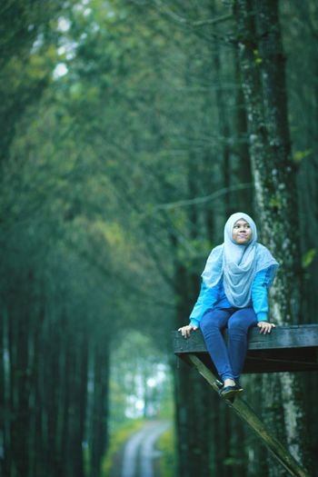Low Angle View Of Thoughtful Young Woman In Hijab Sitting Against Trees At Forest