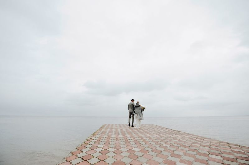 Bride And Bridegroom Walking On Pier In Sea During Wedding Ceremony
