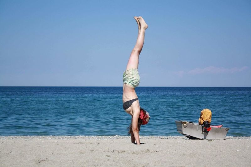 Upside down image of woman exercising on sand at beach
