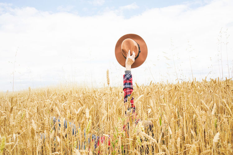 Land Field Cereal Plant Crop  Agriculture Plant Sky Growth Landscape One Person Day Farm Rural Scene Environment Nature Wheat Cloud - Sky Scenics - Nature Real People Beauty In Nature Arms Raised Human Arm Countryside Country Hat