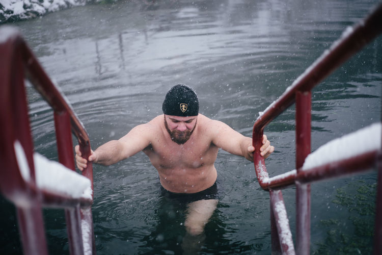 Shirtless man wading in lake