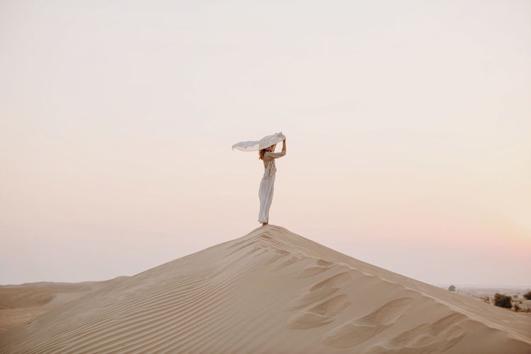 Woman holding scarf in the sand dune in desert