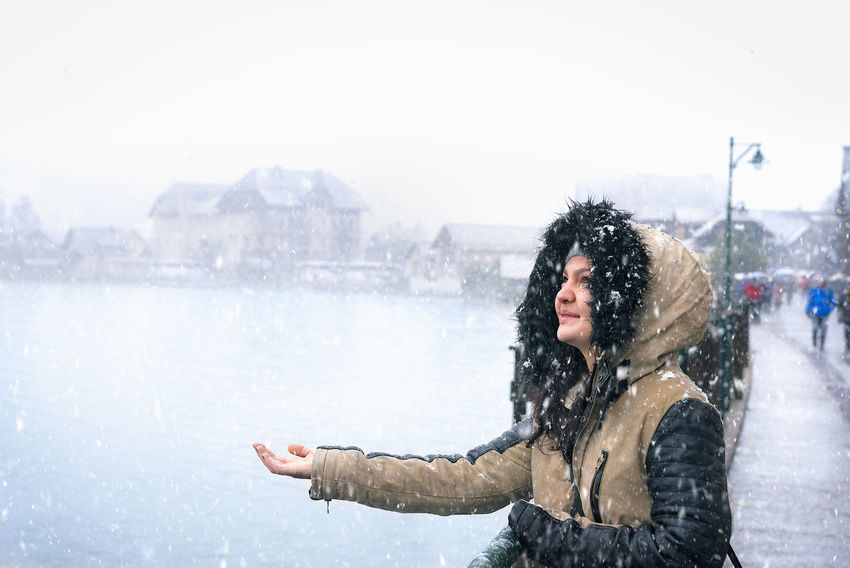 Portrait of a beautiful woman dressed for cold weather, enjoying the snowfall with her hand stretched to catch snowflakes, in the famous Hallstatt town, Austria. Austria Austrian Winter First Snow Cold Temperature Early Winter Enjoyment First Snowfall Hallstatt Hallstatt, Austria Happiness Leisure Activity Nature One Person Snow Snowing Warm Clothing Water Winter Women Young Women