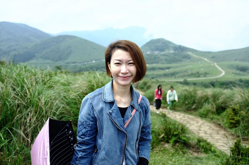 Portrait of young woman standing on field against mountains