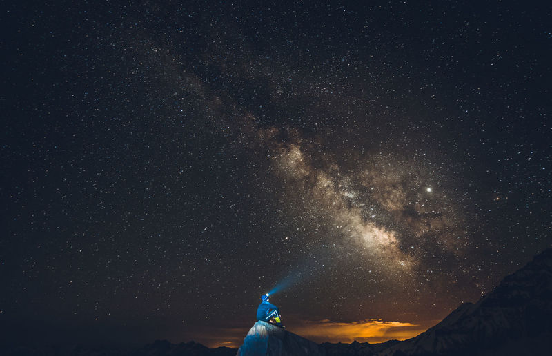 Low angle view of man sitting on cliff against milk way in sky at night