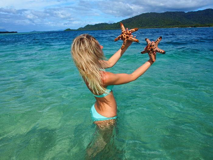Woman Holding Starfish In Sea