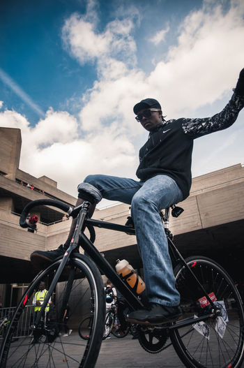 Bicycle Casual Clothing Cloud - Sky Critical Mass Day Fixedgear Full Length Goon Leisure Activity Lifestyles Looking At Camera Low Angle View Mid Adult One Person Outdoors People Portrait Real People Sitting Sky Wheelchair Young Adult Young Men