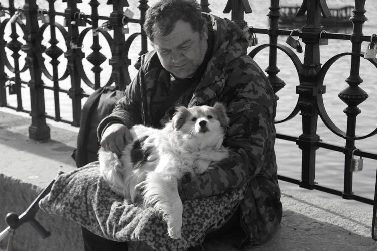 Mammal Domestic Animals Pets Dog Canine Real People Sitting One Person Adult Men Pet Owner Warm Clothing Front View Day Homeless Homelessman Cold Weather Traveling Prague Riverside Portrait Daylight One Animal Spending Time HUMANITY