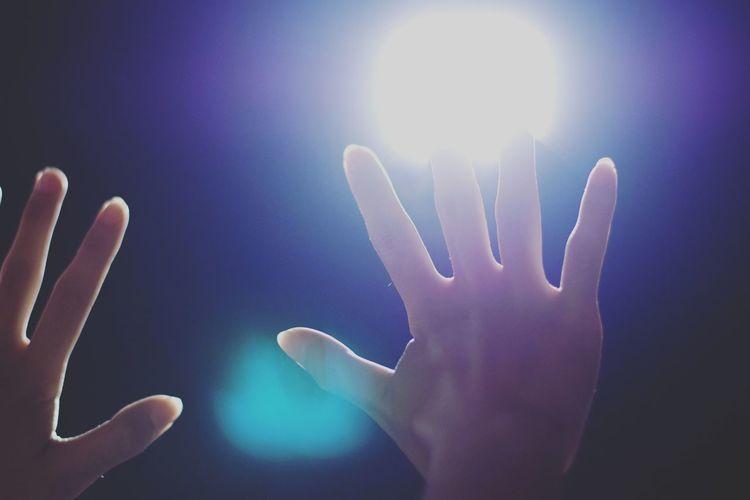 Close-up of hands against illuminated light