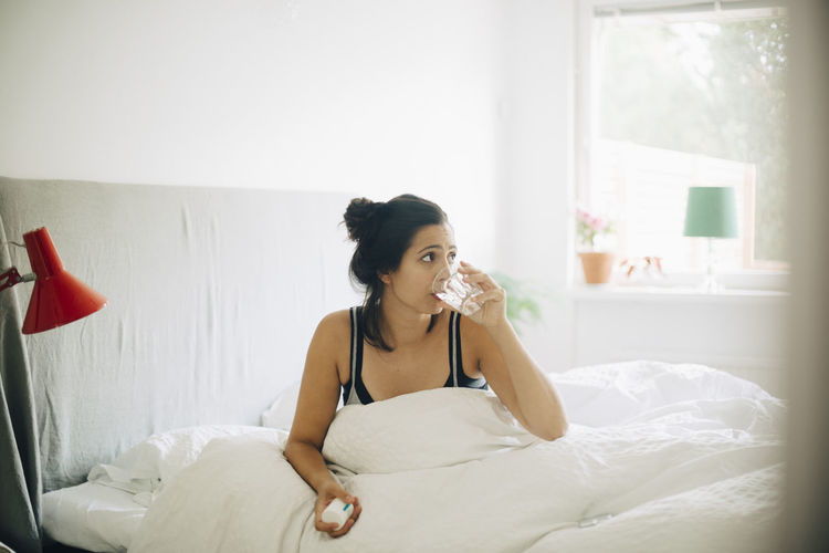 Young woman looking away while sitting on bed at home